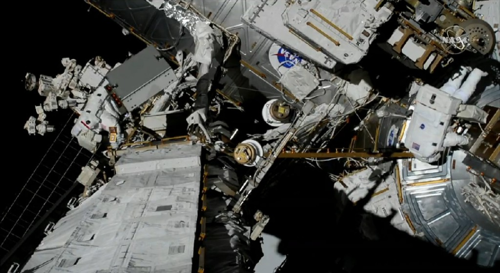NASA Astronauts Christina Koch (EV1 - red stripe) and Jessica Meir carrying out the first all-woman spacewalk on Friday 18th October, 2019 and making history [image: NASA TV screenshot]