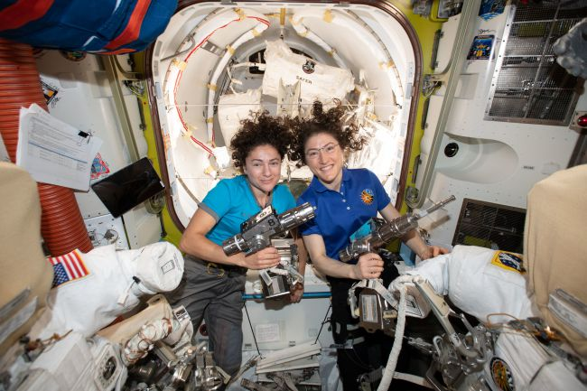 NASA Astronauts Jessica Meir [L] and Christina Koch [R] on 15th October 2019 preparing for their joint spacewalk,  holding the Pistol Grip Tools that they will use to exchange a